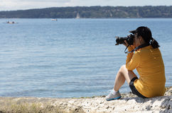 Woman photographer taking photos of calm lake during summer time royalty free stock images