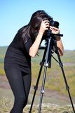 Woman Photographer Taking Photos with Digital Camera and Tripod royalty free stock images