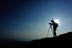Woman photographer taking photos at mountain peak Royalty Free Stock Photos