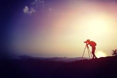 Woman photographer taking photos at mountain peak Royalty Free Stock Image