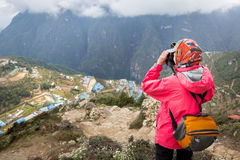 Woman photographer taking picture Namche Bazaar mountain village. Stock Photos