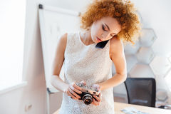 Woman photographer using vintage camera and talking on mobile phone Royalty Free Stock Photo