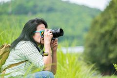 Woman photographer wear sunglasses and holding camera and take a picture of green grass field,Travel wanderlust concept,Banner siz. E leave space for adding text Stock Photography