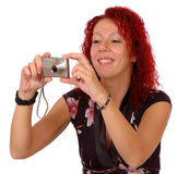 Woman photographing. Woman taking a photo using a point and shoot camera, isolated on white background Royalty Free Stock Photography