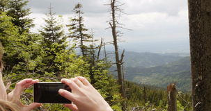Woman photographing from above the beautiful forest stock video