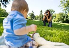 Woman Photographing Baby Boy In Park. Happy young women photographing baby boy through camera in park Stock Images