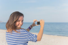 Woman photographing the beach Royalty Free Stock Photography