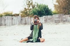 Woman photographing on the beach. Young woman photographing on the beach Royalty Free Stock Images