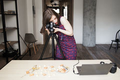 Woman photographing cookies set in studio. Woman photographing cookies set on white background. Food photographer working at studio with sweets royalty free stock image