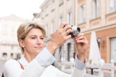 Woman photographing through digital camera in city Royalty Free Stock Images