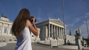 Woman photographing european architecture. Travelling in Europe. Woman takes pictures of historical attraction on sightseeing tour stock footage