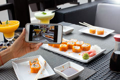 Woman photographing food served in sushi bar with mobile phone. Royalty Free Stock Photography