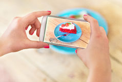 Woman photographing food with smartphone Stock Photography