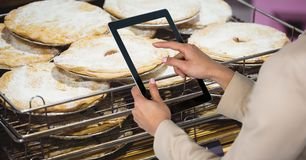 Woman photographing food through tablet computer in grocery store. Digital composite of Woman photographing food through tablet computer in grocery store Royalty Free Stock Photos