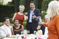 Woman Photographing Friends At Dinner Party Stock Photos