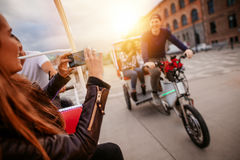 Woman photographing friends on tricycle ride. Royalty Free Stock Images