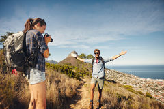 Woman photographing her boyfriend while hiking Royalty Free Stock Images