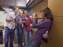 Woman photographing her friends in the kitchen Stock Photo