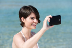 Woman photographing herself on her mobile Royalty Free Stock Images