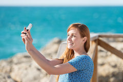 Woman photographing herself with a mobile Royalty Free Stock Images