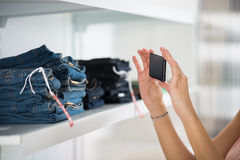 Woman Photographing Jeans In Retail Store Royalty Free Stock Photo