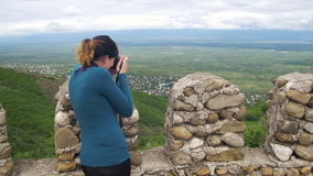 Woman Photographing Landscape. View from an Ancient Fortress on the City of Signaghi, Georgia. Top View from the city and mountains. Clouds above the mountains stock video