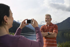 Woman Photographing Man Against The Mountains. Woman photographing mature man with mountains in the background Stock Photo
