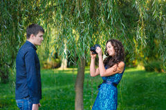 Woman photographing a man on camera Stock Photography