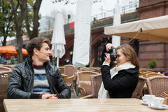 Woman Photographing Man At Outdoor Restaurant Stock Images