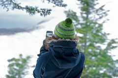 Woman photographing nature. By her smartphone, traveler girl taking picture of the mountains covered with snow, enjoying active winter holidays Royalty Free Stock Photography