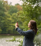 Woman photographing nature in the woods Royalty Free Stock Image