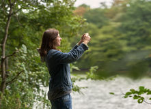 Woman photographing nature in the woods Royalty Free Stock Photos