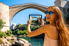 Woman photographing old bridge in Mostar city Royalty Free Stock Photography