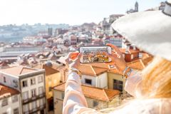 Photographing Porto city in Portugal. Woman photographing with phone cityscape view on the old town of Porto city in Portugal Royalty Free Stock Photo