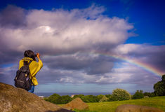 Woman photographing rainbow Royalty Free Stock Photo