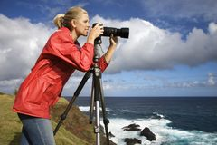 Woman photographing scenery in Maui, Hawaii. Caucasian mid-adult woman looking through camera on tripod on cliff overlooking ocean in Maui, Hawaii Royalty Free Stock Photo