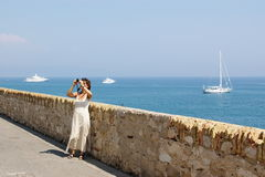 Woman photographing by sea. Woman taking photographs by sea in summer with yachts sailing in background Stock Photos