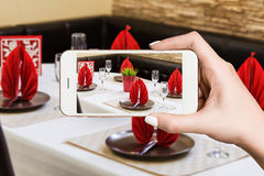 Woman photographing on smartphone, interior of modern restaurant Royalty Free Stock Photos