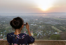 Woman photographing sunset Stock Photo