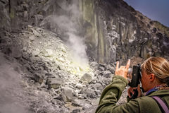 Woman photographing volcano crater Stock Photos