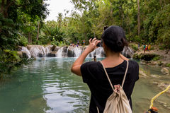 Woman photographing waterfalls. royalty free stock image