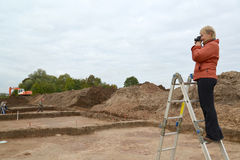 The woman photographs archeological excavations, standing on a ladder Royalty Free Stock Images