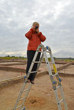 The woman photographs archeological excavations, standing on a ladder Royalty Free Stock Photo
