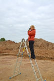 The woman photographs archeological excavations, standing on a ladder Stock Photography