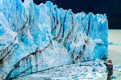 Woman photographs the blue ice wall. Woman photographs phenomenon of nature - the blue ice wall. The fantastic glacier Perito Moreno, in the Patagonia. The royalty free stock photos