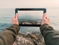 Woman photographs coast on tablet PC Royalty Free Stock Photos