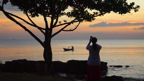 The woman photographs a decline with the boat on the smartphone. Boat on open sea sunset horizon. On this video you can see as the small rybatsky boat floats on stock footage