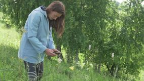 A woman photographs flowers in a field on a mobile phone. Woman in the rain photographs wildflowers stock video footage