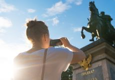 Woman taking pictures of monument. Woman photographs a monument to Peter the first in Saint-Petersburg stock photography