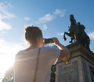 Woman taking pictures of monument. Woman photographs a monument to Peter the first in Saint-Petersburg royalty free stock photography
